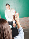 College Student Raising Hand To Answer In. Rear view of young college student raising hand to answer in classroom Royalty Free Stock Photo