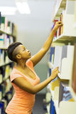 College student reaching book. Young african college student reaching for a book in library royalty free stock photography