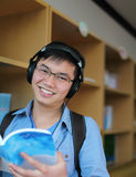 College student reading book. And listening music on library Royalty Free Stock Photography