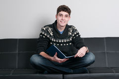 College student reading a book. Teenager sitting on a couch reading a book Royalty Free Stock Images