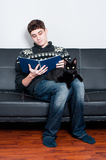 College student reading a book with his pet cat. Teenager sitting on a couch reading a book Royalty Free Stock Photo