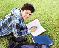College student reading over grass. Male Indian / Asian college student lying / studying over the grass Royalty Free Stock Images
