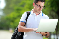 College student reading a subject on his laptop Stock Image