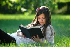 College student reads book in park Royalty Free Stock Images