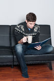 College student relaxing drinking tea and reading Royalty Free Stock Image