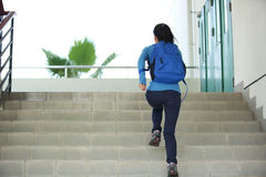 College student running up stairs royalty free stock image
