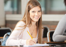 College Student Sitting At Desk In Classroom Royalty Free Stock Image