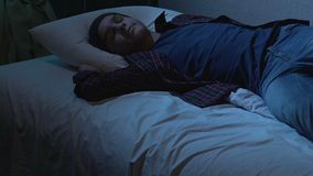College student sleeping in cloth on bed after student party, dreams at night. Stock footage stock video