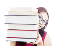 College student smiling behind books. Portrait of female college student smiling behind thick books Royalty Free Stock Photos