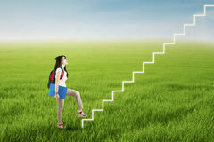 College student stepping up on stairs. To gain her success Stock Photography
