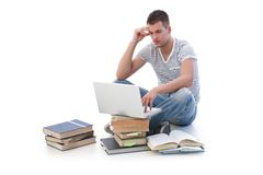 College student studying. College student sitting among books, using laptop, studying Stock Photo