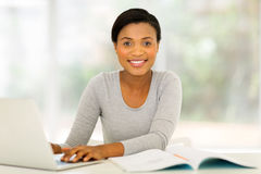 College student studying home. Pretty african american college student studying at home Stock Photography