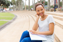 College student studying outdoors. Happy african american college student studying outdoors on campus Stock Image