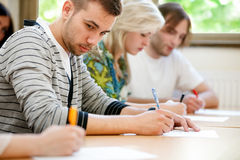 College student trying to copy test. College student trying to copy off a student's test paper Stock Images