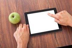 College student using blank digital tablet. Cropped image of male college student using blank digital tablet by green apple on table Royalty Free Stock Photos