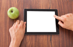 College Student Using Blank Digital Tablet. Cropped image of male college student using blank digital tablet by green apple on table Royalty Free Stock Image