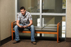 College Student Using Cellphone. Portrait of student using phone inside college campus Royalty Free Stock Image