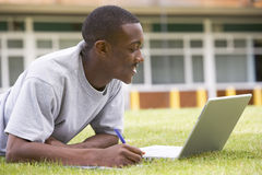 College student using laptop on campus lawn Stock Images