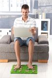 College student using laptop smiling at home. College student sitting in armchair in living room, using laptop, resting legs on artificial grass, smiling Stock Photography