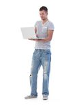 College student using laptop standing. College student browsing internet on laptop, standing, smiling Royalty Free Stock Images