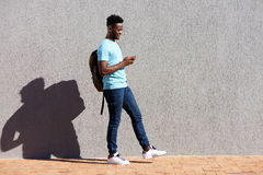 College student walking with bag and mobile phone. Full length portrait of college student walking with bag and mobile phone Royalty Free Stock Photo