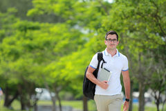 College student walking by at college park. Portrait of handsome college student with backpack and tablet walking by at college park Stock Photography