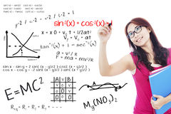 College student write math formula. Portrait of female college student using marker to write math formula on the whiteboard Royalty Free Stock Images