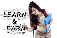 College student writes Learn and Earn Royalty Free Stock Photography
