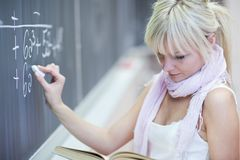 College student writing on the chalkboard Royalty Free Stock Images