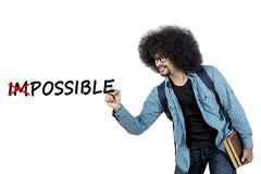 College student writing impossible text on screen. College student writing impossible text on virtual screen while holding book, isolated on white background Royalty Free Stock Image