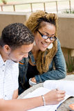 College students. Two african college students study book together outdoors Stock Image