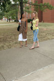College Students. On campus.  Walking, talking on payphone and on cellphone Royalty Free Stock Photo