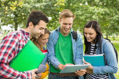 College students with bags and books using tablet PC in park Royalty Free Stock Image