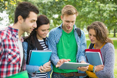 College students with bags and books using tablet PC in park. Group of young college students with bags and books using tablet PC in the park stock photos