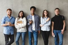 College students with books smiling to camera over grey wall
