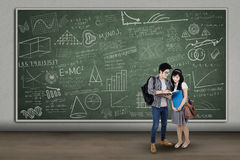 College students in classroom. Happy college students reading a book in classroom Royalty Free Stock Images