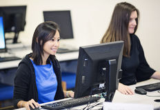 College students in a computer lab. Two college students in a computer lab Royalty Free Stock Photos