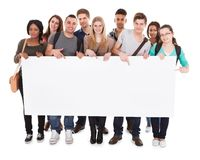 College students displaying blank billboard. Full length portrait of confident multiethnic college students displaying blank billboard against white background Stock Photo