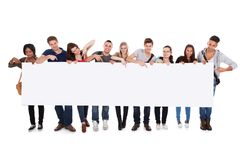 College students displaying blank billboard. Full length portrait of confident multiethnic college students displaying blank billboard against white background Royalty Free Stock Images
