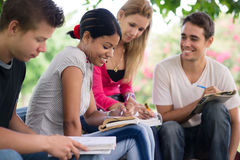 College students doing homeworks in park. Friends and education, group of university students studying, reviewing homework and preparing test Royalty Free Stock Image