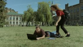 College students enjoying leisure on campus lawn. Concentrated college male student laying down on campus lawn and networking on laptop as his cute girlfriend stock footage