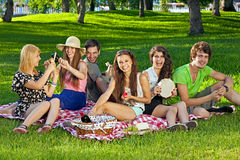 College students enjoying a picnic in the park Stock Photo