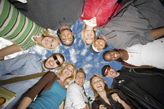 College Students Forming Huddle Against Cloudy Sky Stock Images