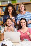 College students gesturing thumbs up in library Stock Photo