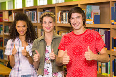 College students gesturing thumbs up in library Stock Image