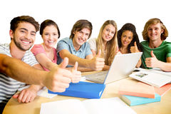 College students gesturing thumbs up in library Royalty Free Stock Photo