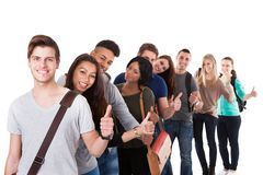 College students gesturing thumbs up in a line. Portrait of college students gesturing thumbs up while standing in a line over white background Royalty Free Stock Photo