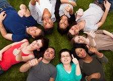 College students gesturing thumbs up while lying on grass. High angle portrait of confident college students gesturing thumbs up while lying on grass Stock Images