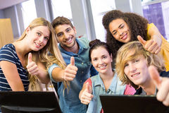 College students gesturing thumbs up. Portrait of happy college students gesturing thumbs up Royalty Free Stock Image