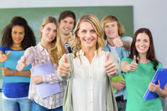 College students gesturing thumbs up. Portrait of happy college students gesturing thumbs up Royalty Free Stock Photography